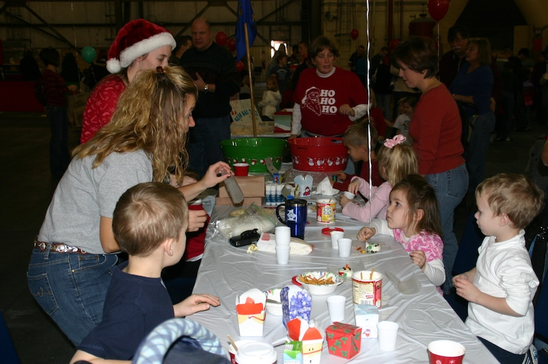 Master Sgt. Glenda Ipock, first sergeant, 964th Airborne Air Control Squadron, helps several children frost cookies and make crafts at the squadron activity tables. Photo courtesy of 1Lt Kinder Blacke.