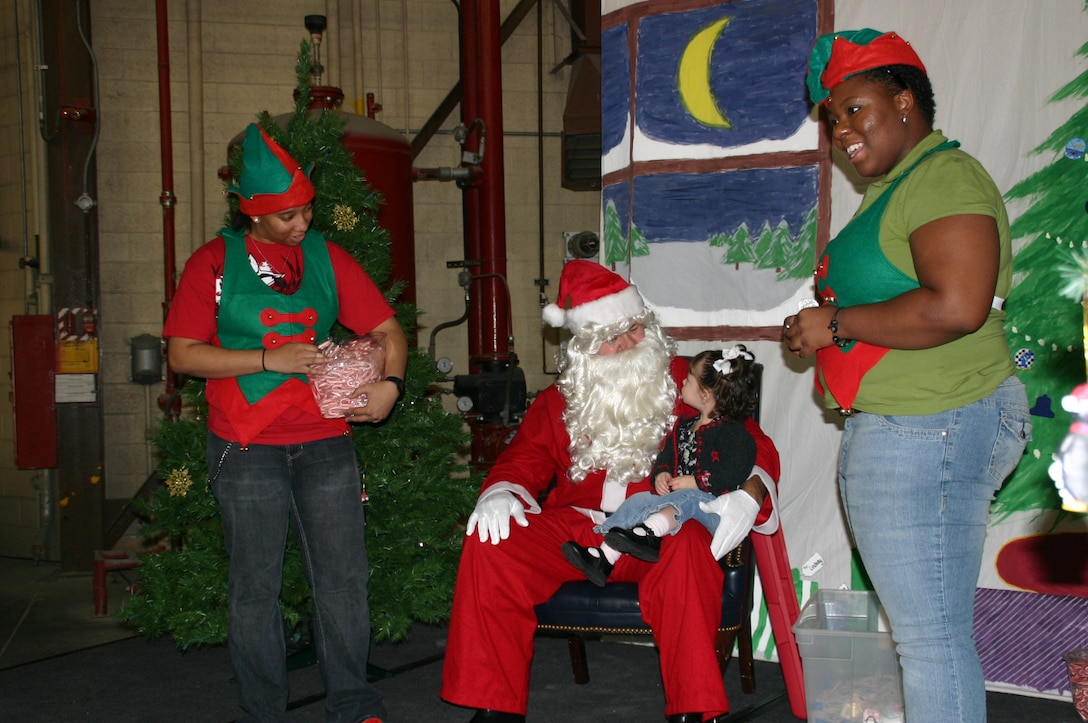 Santa Claus and his elves take time to visit with one of the young members of the 552 ACW family to find out what she would like for Christmas. Photo courtesy of 1Lt Kinder Blacke.