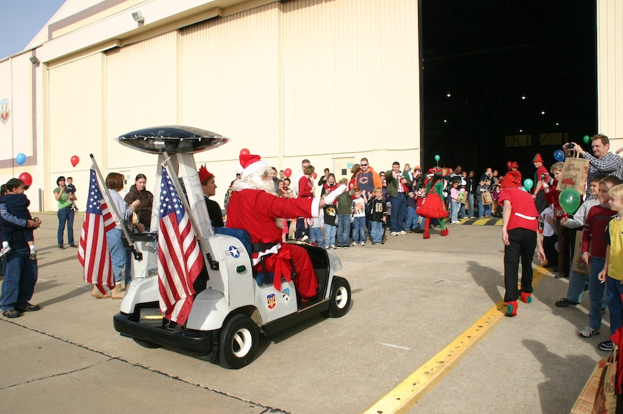 Santa Claus waves to the excited crowd of children and their parents as Col. Pat Hoffman, commander, 552 ACW chauffeurs him into the building in the AWACS golf cart. Photo courtesy of 1Lt Kinder Blacke.