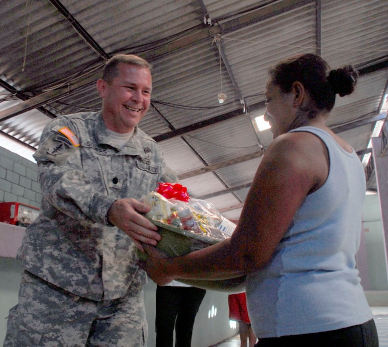 AJUTERIQUE, Honduras - Army Lt. Col. Richard Somers, Joint Task Force-Bravo Army Forces commander, gives a gift basket to a local Dec. 9. The baskets, full of essential food and supplies, were from JTF-Bravo and Southern Command to more than 100 local families who were recently affected by widespread flooding. (U.S. Air Force photo by Staff Sgt. Joel Mease)