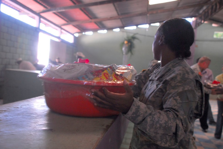 AJUTERIQUE, Honduras - Army Staff Sgt. Jenise Harris, Joint Task Force-Bravo, assists moving food baskets to be given out to more than 100 families here Dec. 9. JTF-Bravo and U.S. Southern Command gave the baskets filled with essential food and supplies to families affected by widespread flooding recently. (U.S. Air Force photo by Staff Sgt. Joel Mease)