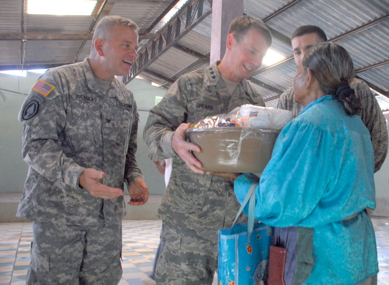 AJUTERIQUE, Honduras - Lt. Gen. Glenn Spears (center), U.S. Southern Command deputy commander, and Col. Richard Juergens (left), Joint Task Force-Bravo commander, give a local a gift basket from servicemembers at Soto Cano Air Base here Dec. 9. More than 100 families received a free basket containing food items and essential supplies as a way for JTF-Bravo to show their support for their community. (U.S. Air Force photo by Staff Sgt. Joel Mease)