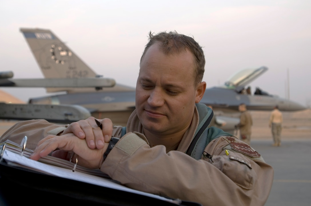 Maj. Curt Grayson fills out paperwork shortly after landing at Joint Base Balad, Iraq, Dec. 10. Grayson's home unit, the Minnesota Air National Guard's 179th Fighter Squadron, will carry the 332nd Expeditionary Fighter Squadron designation while deployed. Grayson, an F-16 Fighting Falcon pilot, is a native of Esco, Minn. (U.S. Air Force photo/Tech. Sgt. Erik Gudmundson)