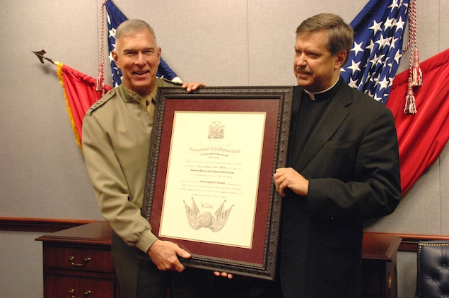 Gen. James T. Conway, commandant of the Marine Corps, presents Father Peter F. Vasko with an Honorary Marine certificate Dec. 12 inside the Pentagon. Vasko has served as the unofficial chaplain for Jerusalem's Marine Security Guard detachment for the past 18 years.::r::::n::