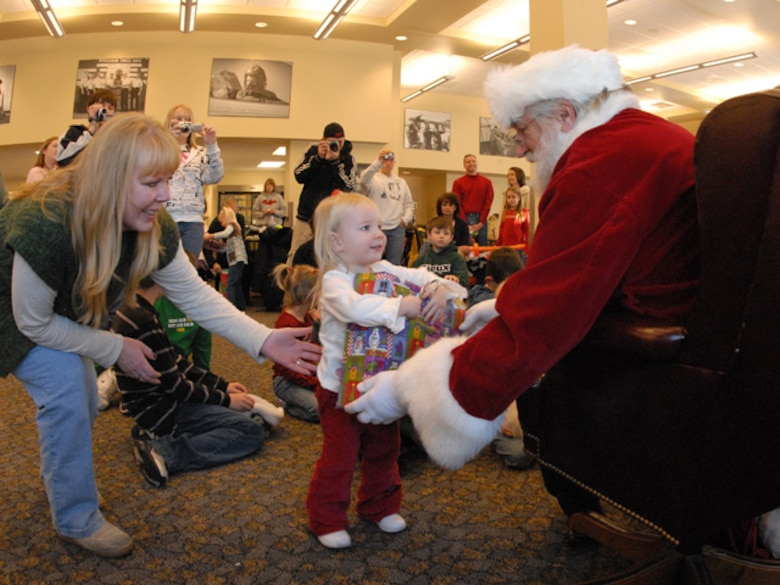 Master Sgt. Susan Schroeder of the 119th Wing assists her daughter as she takes a gift from Santa during the annual 119th Wing Children's Christmas party at the North Dakota Air National Guard on December 8, 2007.