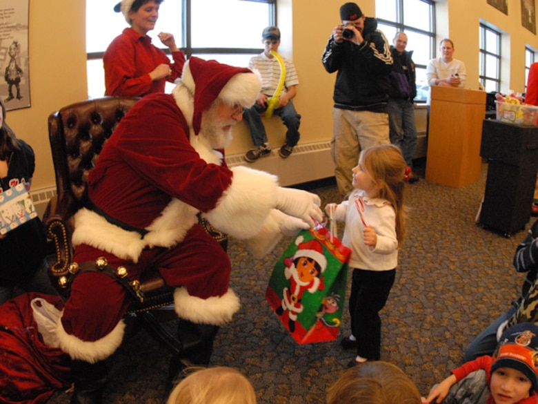 Elise, three-year old daughter of Master Sgt. Eric Johnson of the 119th Wing, receives a present in a 'Dora the Explorer' gift bag from Santa at the 119th Wing Children's Christmas Party at the North Dakota Air National Guard on December 8, 2007.