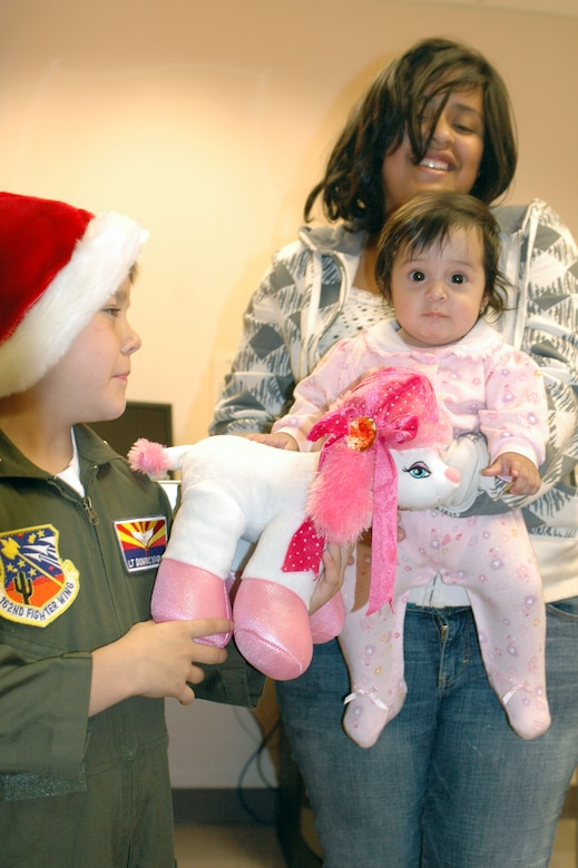 PHOENIX – Honorary 162nd Fighter Wing member Dominic Magne, 7, gives a stuffed animal to a baby at Phoenix Children's Hospital Dec. 11. The Tucson-based Guard unit held a gift drive in November and December resulting in more than 250 toys, games, books and DVDs. Every child received a gift with extras donated to the hospital for future patients. (Air National Guard photo by Capt. Gabe Johnson)