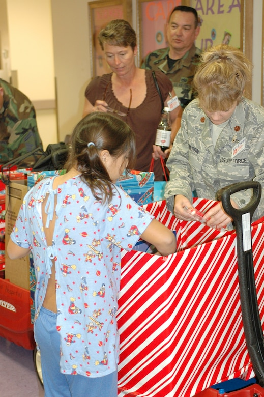 PHOENIX – Barb Gavre, Master Sgt. Dave Morgan and Maj. Sandy Wilson help a patient at Phoenix Children's Hospital search for a gift from the 162nd Fighter Wing's collection of donations Dec. 11. Wing members visited every floor and playroom in the hospital to ensure every child received a gift. The Tucson-based Guard unit held a gift drive in November and December resulting in more than 250 toys, games, books and DVDs. (Air National Guard photo by Capt. Gabe Johnson)