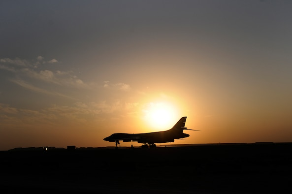 The setting sun silhouettes a B-1B Lancer, Dec. 12, at an undisclosed air base in Southwest Asia.  Carrying the largest payload of both guided and unguided weapons in the Air Force inventory, the multi-mission B-1 is the backbone of America's long-range bomber force. It can rapidly deliver massive quantities of precision and non-precision weapons against any adversary, anywhere in the Central Command area of responsibility.  (U.S. Air Force photo by Tech. Sgt. Michael Boquette/Released)