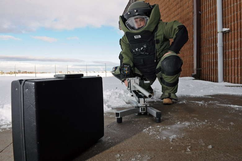 Senior Airman Alicia Goodner, 28th Civil Engineer Squadron Explosive Ordinance Disposal operator, demonstrates using a Percussion Actuated non-electric disrupter here, Dec. 11. PAN disrupters are designed to remotely disrupt explosive devices. (US Air Force photo/Airman 1st Class Corey Hook)