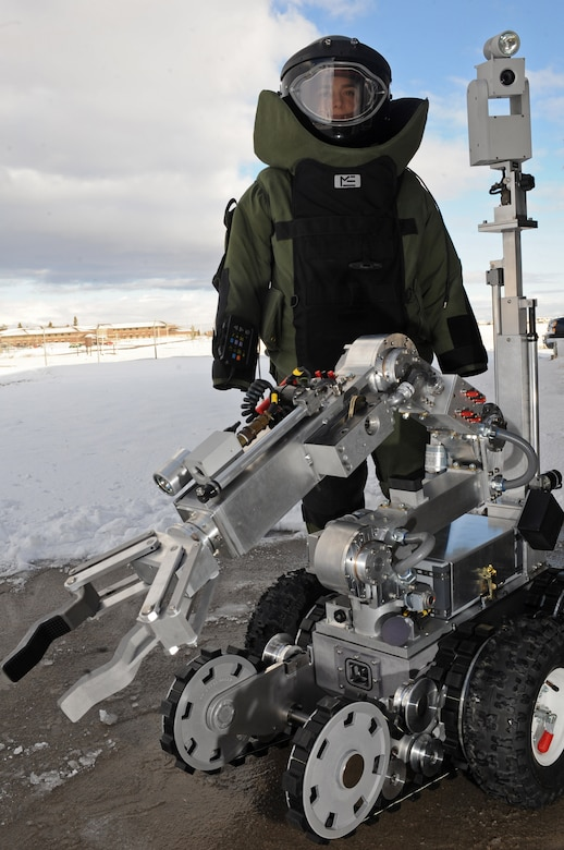 Senior Airman Alicia Goodner, 28th Civil Engineer Squadron Explosive Ordinance Disposal operator, stands beside a ANDROS F6A Robot here, Dec. 11. The robot is equipped with several television cameras for remote viewing and a dexterous arm for hazardous tasks. (US Air Force photo/Airman 1st Class Corey Hook)