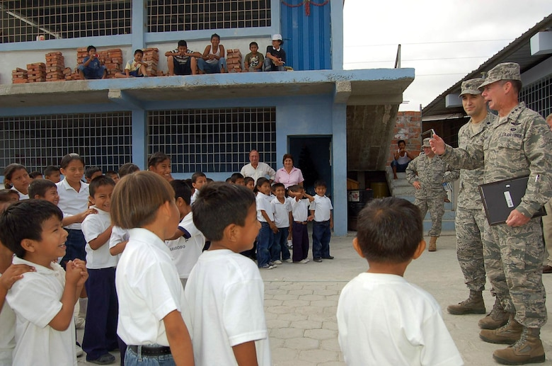 Lt. Gen. Glenn F. Spears (right) and Lt. Col. David Keesey present a gift of $6,000 in school supplies from the Southern Command's Humanitarian Assistance Program to children Dec. 10 at the San Juan Elementary School in Ecuador. The donation was part of a weeklong holiday tour to engage with forward deployed personnel and assist nearby communities in seven Latin American countries during the holiday season. General Spears is the Southern Command deputy commander and Colonel Keesey is his executive and translator on the trip. (U.S. Air Force photo/Tech. Sgt. Matthew McGovern)