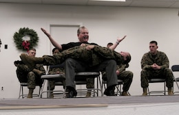 CAMP H.M. SMITH, Hawaii -- Comedian Ken Whitener demonstrates the power of hypnosis by having Lance Cpl. Jessica Perry, MarForPac combat lithographer, make her body straight as a board and strong e