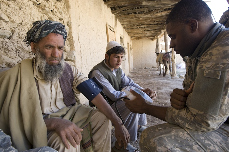 """Senior Airman Courtney Thompson, a Provincial Reconstruction Team medic in Afghanistan, examines an Afghan man at a village medical outreach clinic.  Air Force Chief of Staff Norton Schwartz announced Dec. 17 that an Airman previously categorized as filling an """"in lieu of"""" or ILO tasking now would be referred to as filling a """"joint expeditionary tasking,"""" or JET.  He stated that the term JET reinforces the Air Force's commitment to the joint fight as an equal member of the joint team. (U.S. Air Force photo/Master Sgt. Keith Brown)"""