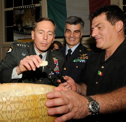 Gen. David Petraeus, United States Central Command commander, samples a piece of the legendary Parmigiano-Reggiano while Luigi and Brig. Gen. Enrico P. Bassignano, the Italian Senior Representative from CENTCOM, stand by to watch during the Coalition International Night held here in Hangar 1, Dec. 16. This year's event marks the 5th anniversary of the annual tradition that allows military members and families to become more familiar with various native cuisines, customs and dress of the 63 different countries represented in the U.S. Central Command Coalition Village. During this event many Coalition members and their families volunteered to cook some of their countries favorite or famous cuisines to share. The event ended with the United States Central Command commander, Gen. David Petraeus, giving a thank you speech to all those who came out.
