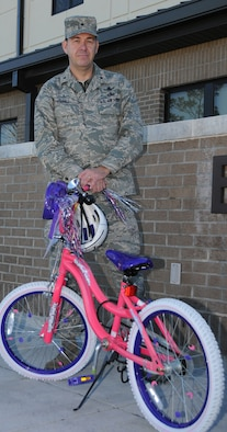 General Touhill stands in front of a child's bicycle to remind Keesler members of the lives they endanger if they choose to drink and drive.  General Touhill has pledged to ride the bicycle to wing headquarters if the wing goes 81 consecutive days without a DUI incident.  He reminds everyone to have a safe holiday.  (U.S. Air Force photo by Kemberly Groue)