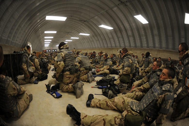 Airmen Basic trainees take a break inside a hard shelter after inspecting each others body armor during the five-day deployment exercise called the Basic Expeditionary Airman Skills and Training, or BEAST, which kicked off Dec. 15 at Lackland Air Force Base, Texas. The BEAST is the newly built complex added into the extended, 8.5-week Basic Military Training curriculum that began Nov. 5. (U.S. Air Force photo/Staff Sgt. Desiree N. Palacios)