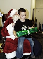 Grant Glasgow, 6, receives his gift from Santa Claus at the U.S. Marine Corps Forces, Pacific Headquarters and Service Battalion holiday party at the Pollock Theater Dec. 18. Children enjoyed time with Santa, crafts and face painting.