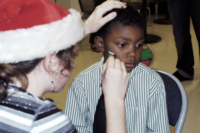 Cameron Ray, 7, gets his face painted at the U.S. Marine Corps Forces, Pacific Headquarters and Service Battalion holiday party at the Pollock Theater Dec. 18. Children received gifts from Santa, participated in crafts and face painting.