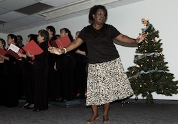Jeannette Powell-Campbell, MarForPac administration chief dances as the Honolulu Blend Chorus sings traditional holiday songs during the U.S. Marine Corps Forces, Pacific Headquarters and Service Battalion holiday party at the Pollock Theater Dec. 18.