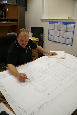 ATA's Will Vodra studies original hand drawings and calculations of the north leg of one of the test cells at Tunnel 9. The test cell rests on steel v-groove wheels. These wheels allow the nozzle to separate from the test cell and heater for preparations between tests. Vodra was trying to understand the original estimated supporting wheel loads in preparation for an upcoming test while replacing a broken wheel to determine if the calculations underrated the real test cell weight. (Photo by Philip Lorenz III)