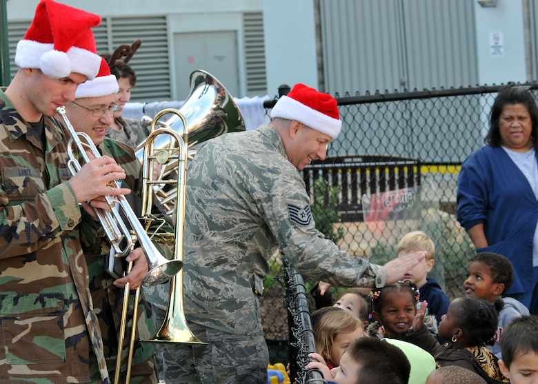 "Tech. Sgt. Edward Schubert gives ""hi 5's"" to audience members as Senior Airman James Lantz plays along. The meet-and-greet took place during the Band of the Golden West's performance at the Child Development Center, Los Angeles AFB, Dec. 15. (Photo by Atiba Copeland)"