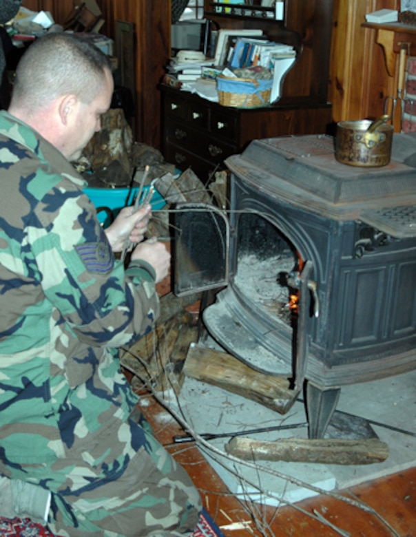 Tech. Sgt. John Bober of the 157th Air Refueling Wing, Pease Air National Guard Base, N.H. starts a fire for a local Stratham resident who was left without power due to the ice storm that hit the area six days earlier. (U.S. Air Force photo/1st Lt. Sherri Pierce)