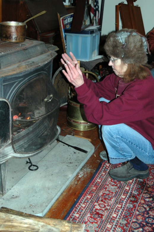 Patricia Olson of Stratham, N.H., warms herself by the fire.  The 157th Air Refueling Wing assisted the town with welfare checks during the ice storm that left Olson without power and heat for 6 days.  (U.S. Air Force photo/1st Lt. Sherri Pierce)