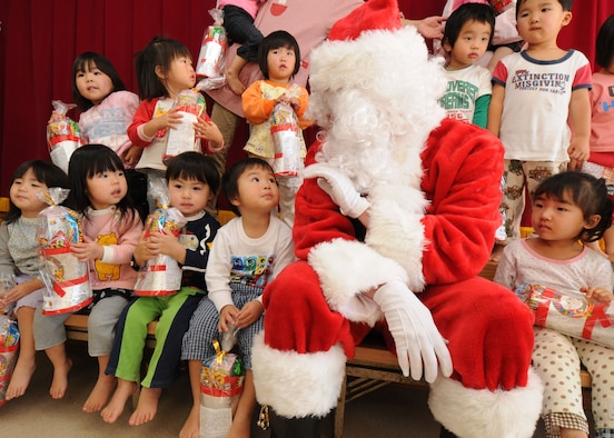 "YOKOTA AIR BASE, Japan --  Airman Sean ""Santa"" Martin from the 374th Airlift Wing Public Affairs office takes a photo with children at the Taisho elementary school, Hinoda City, Dec. 18. While there, Airman Martin also handed out gifts and answered any question they had for Santa.