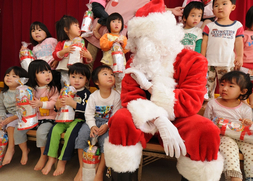 """YOKOTA AIR BASE, Japan --  Airman Sean """"Santa"""" Martin from the 374th Airlift Wing Public Affairs office takes a photo with children at the Taisho elementary school, Hinoda City, Dec. 18. While there, Airman Martin also handed out gifts and answered any question they had for Santa.(U.S. Air Force photo by Senior Airman Veronica Pierce)"""