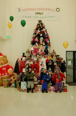 """A nearly 14-foot """"can tree"""" decorated by the 523rd Electronics Maintenance Group, towers nearly 14 feet in Bldg. 5, decorated with sweaters, coats, scarves, sweatshirts, shoes, toys and food items. The five 309 EMXG squadrons held a competition to collect food items and display them in a Christmas setting, and the 523rd entry was selected as """"most creative.""""  The more than 2,200 food items, clothing and toys collected will be taken to local charities."""