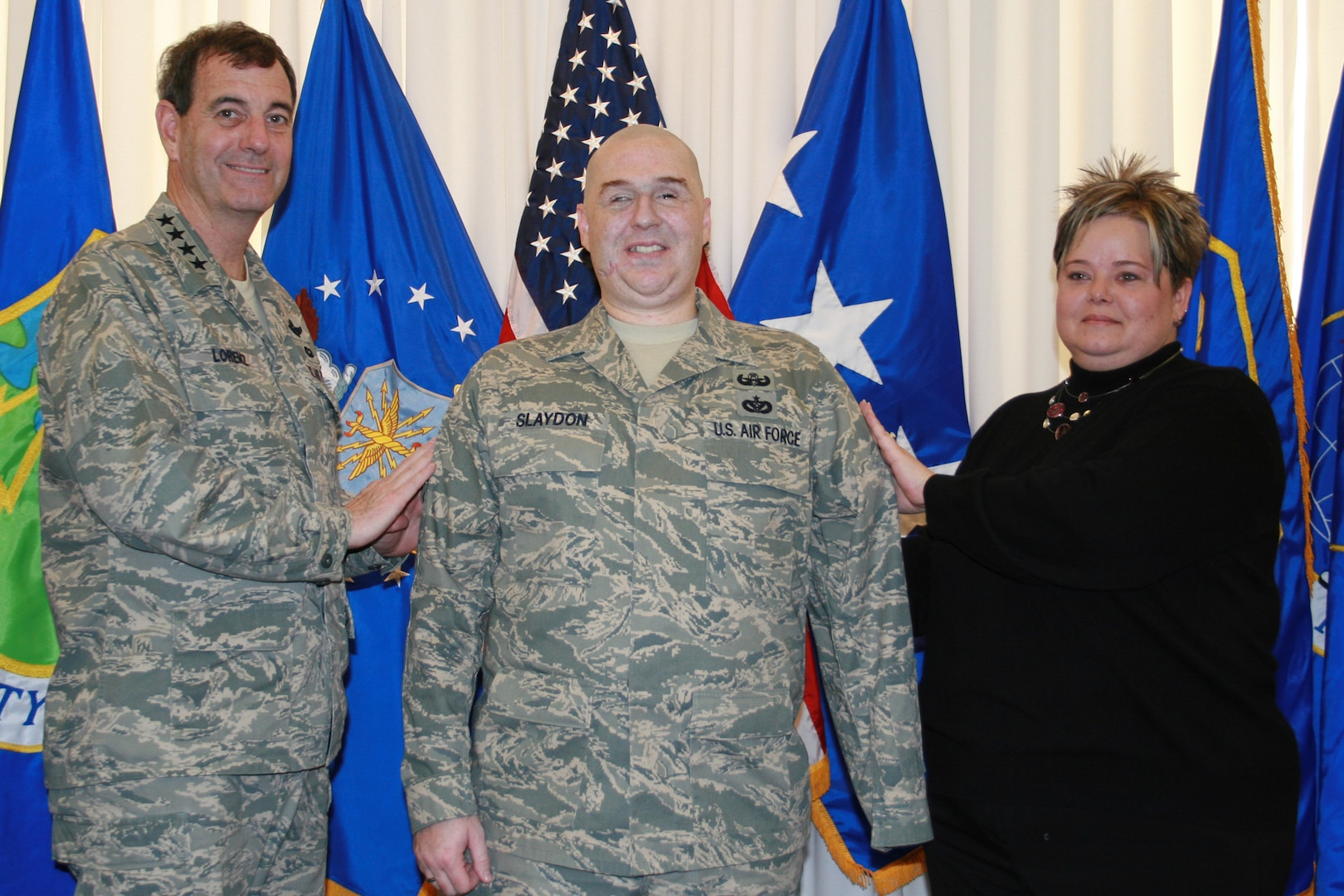 Gen. Stephen Lorenz (left), Air Education and Training Command commander, promotes Staff Sgt. Matt Slaydon to technical sergeant through the Stripes To Exceptional Performers, or STEP, program Dec. 19 at AETC Headquarters. Sergeant Slaydon's wife, Annette, helps the general tack on the stripe. General Lorenz conducted the on-the-spot promotion on behalf of Brig. Gen. Kurt Neubauer, 56th Fighter Wing commander, which is Sergeant Slaydon's home unit. He has been in San Antonio for more than a year receiving medical care for wounds he suffered Oct. 24, 2007, in Iraq when a bomb exploded next to him during his duty as an explosive ordnance disposal specialist.  Sergeant Slaydon received the promotion for the extensive Air Force ambassadorship and mentorship he has conducted during his year-long recovery. (Photo by Michelle Deleon)