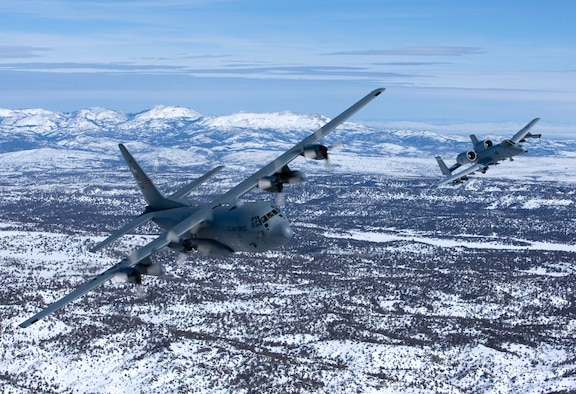 An A-10A Thunderbolt II and a C-130E Hercules, both from the 124th Wing Idaho Air National Guard, fly in formation over Idaho's Sawtooth Mountain Range. (Photo by Mr James Haseltine)