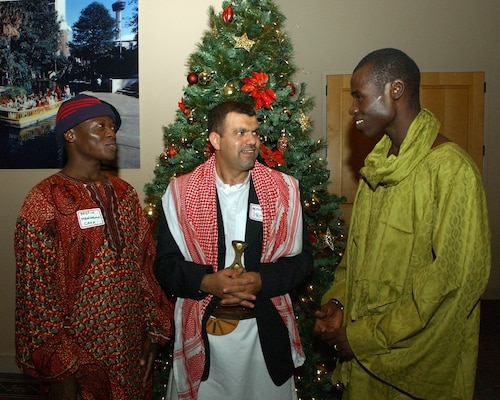 Master Sgt. Bertin Mbaidoloum, Chad, Maj. Yaha Alyusrei, Yemen, and First Lt. Ibra Diakhate, Senegal, discuss holiday traditions during the Defense Language Institute English Language Center holiday social Dec. 13 at Lackland Air Force Base, Texas. The DLIELC provides English language training to international military students while giving them opportunities to see and experience American culture. (USAF photo by Alan Boedeker)
