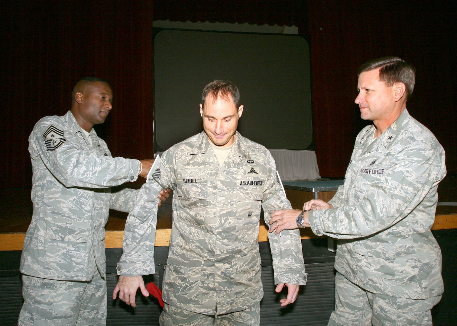 Chief Master Sgt. Juan Lewis (left), 37th Training Wing command chief, and Brig. Gen. Len Patrick, 37th TRW commander, give Staff Sgt. Nicholas Seibel technical sergeant stripes Dec. 16. Sergeant Seibel, 342nd Training Squadron, received an immediate promotion as part of the Stripes for Exceptional Performers Program. (USAF photo by Robbin Cresswell)