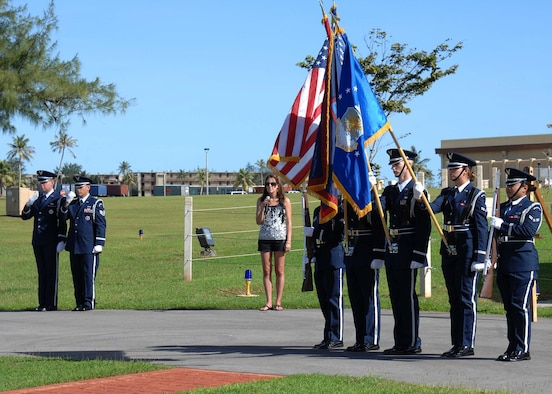 ANDERSEN AIR FORCE BASE, Guam -- The Team Andersen Honor Guard present the flags as Airman 1st Class Heather Wells, 36th Operations Support Squadron, sings the National Anthem at the Arc Light Memorial Park here for the Operation Linebacker II Ceremony Dec. 18. Members of the 36th Expeditionary Bomb Squadron sponsored this year's ceremony, commemorating its 36th anniversary. (U.S. Air Force photo by Senior Airman Sonya Croston)