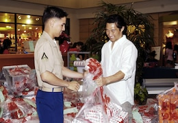 'Lost' actor Daniel Dae Kim hands a bag full of toys to Lance Cpl. Isaac Yuen at Kahala Mall here Dec. 22. Kim decided to make a generous donation to the Marine Corps Reserve's Toys for Tots campaign after hearing it is falling short of its goal this year, he said.