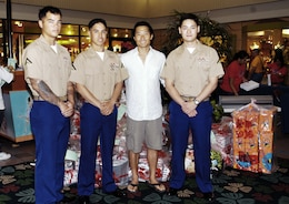 Lance Cpls. Byron Cheek-Enriquez, Isaac Yuen, and Kenji Conley pose with 'Lost' actor Daniel Dae Kim after he donated 500 new toys to the Marine Corps Reserve's 2008 Toys for Tots campaign at Kahala Mall here Dec. 22. After hearing that the campaign was short of its goal this year, Kim wanted to do his part to help the less-fortunate, he said.