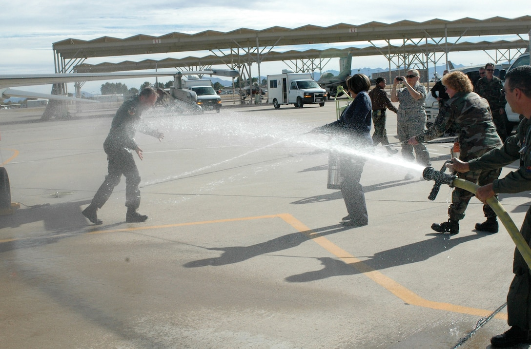 """Brig. Gen. Rick Moisio, 162nd Fighter Wing commander, is hosed down by Master Sgt. Kerri Lane, Chief Master Sgt. Nikki Uremovich and Col. Jose Salinas after his final flight, or """"fini"""" flight, here Dec. 19. The general is a command pilot with more than 30 years of experience and 6,000 flying hours mostly in fighter aircraft. He joined the 162nd in 1984 and assumed command of the unit in 2004. Following the fini flight, Guardsmen here held a farewell event for the commander who will depart the wing for another assignment in February. (Air National Guard photo by Capt. Gabe Johnson)"""