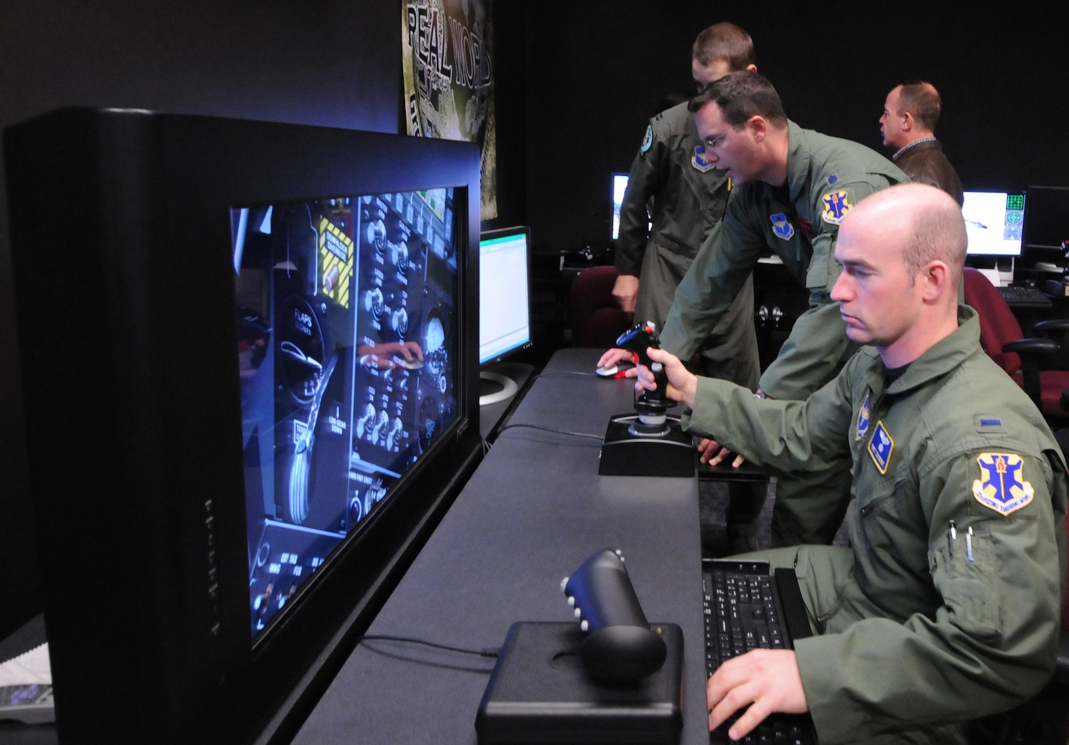 First Lt. Bret Saubert (right), 563rd Flying Training Squadron UAS student pilot, learns to integrate air power on a cyber-based simulation in the training lab at the UAS Fundamentals Course. (photo by Rich McFadden)