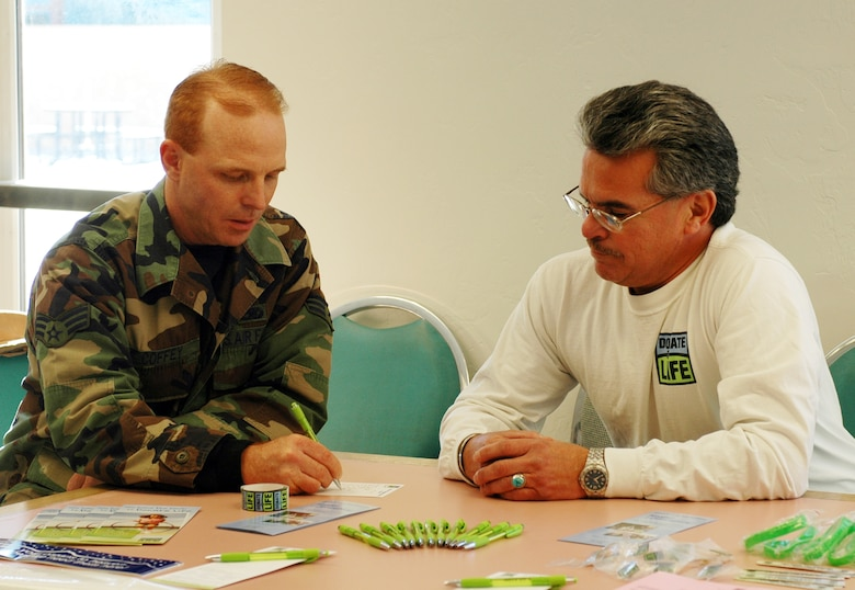 John Salazar Jr., volunteer for the Donor Network of Arizona, assists 162nd Maintenance Squadron member Senior Airman Scott Coffey with filling out a donor application during the December drill. John is a cornea recipient benefiting from the donor network and he's the son of retired 162nd member John Salazar. (Air National Guard Photo by Staff Sgt. Desiree Twombly)