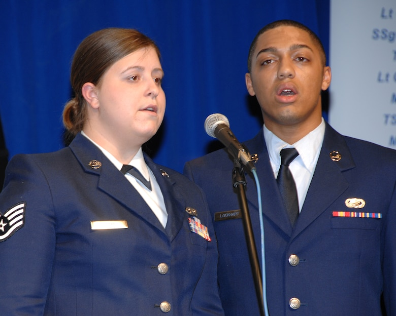 Staff Sgt. Karly Vogel, 133rd Airlfit Wing Headquarters, and Airman First Class David Lockhart, 133rd Mission Support Squadron, sing the National Anthem during the 2008 Wing Recognition Ceremony in a hangar on the St. Paul Air National Guard Base on Dec. 13, 2008. (USAF photo by Tech. Sgt. John Wiggins)