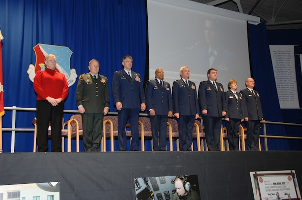 Distinguished guests and leadership from the 133rd Airlift Wing take their place on stage to begin the 2008 Wing Recognition Ceremony in a hangar on the St. Paul Air National Guard Base on Dec. 13, 2008. From left to right, Minnesota Lieutenant Governor Carol Molnau, Minnesota Adjutant General, Maj. Gen. Larry Shellito, 133rd AW Commander, Col. Greg Haase, 133rd Medical Group Commander, Dr. (Col.) Dave Hamlar, 133rd Operations Group Commander, Col. Bob Cayton, 133rd Maintenance Group Commander, Col. Chuck Rodke, 133rd Mission Support Group Commander, Lt. Col Deon Ford, and 133rd AW Command Chief, Chief Master Sgt. Dave Speich all wait for the presentation of the colors. Projected on the screen behind them is the image of 2nd Lt. Christina Hubert, 133rd Operations Support Flight, who introduced them to an audience of over 1,000 Airmen, family members and others. (USAF photo by Tech Sgt. John Wiggins)