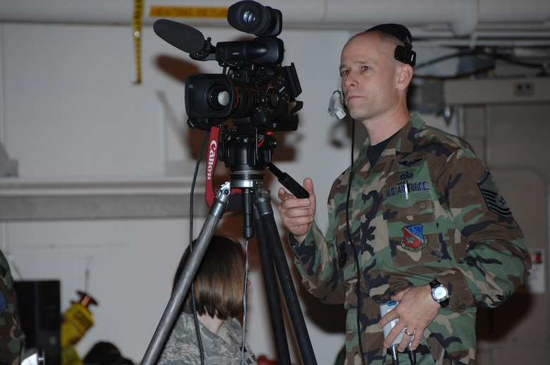 Tech. Sgt. Greg Wohlfeil, 133rd Communications Flight, operates one of the video cameras used to project images of presenters and award recipients onto two large screens for over 1,000 audience members in a hangar during the 133rd Airlift Wing Recognition Ceremony on Dec. 13, 2008. The Minnesota Air National Guard unit in St. Paul holds a ceremony every year recognizing the accomplishments of the Airmen, their families, and others in the community who make the 133rd AW very successful. . (USAF photo by Tech. Sgt. John Wiggins)