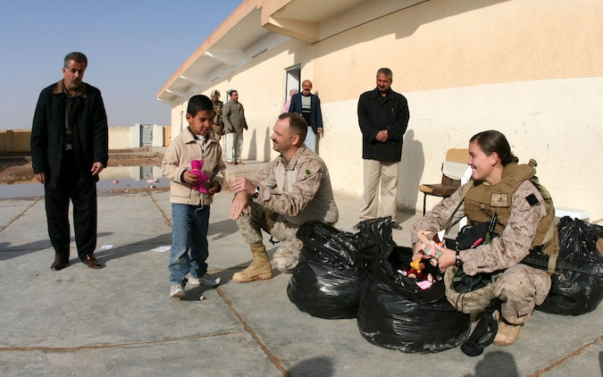 At Mekasid Primary School in Rutbah, Iraq, 1st Sgt. Clark Rhiel (center), the company first sergeant for Headquarters and Service Company, 2nd Battalion, 25th Marine Regiment, Regimental Combat Team 5, and Petty Officer 2nd Class Bridget Shanahan, a corpsman with Shock and Trauma Platoon, 2nd Combat Logistics Battalion, pass out toys to students Dec. 23. The Marines and sailors also brought snacks and soccer balls to the students. ::r::::n::