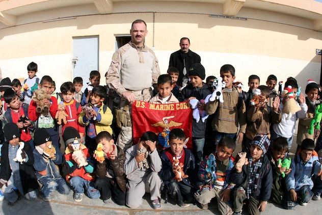 First Sgt. Clark Rhiel (center), the first sergeant for Headquarters and Service Company, 2nd Battalion, 25th Marine Regiment, Regimental Combat Team 5, gathers second grade students for a photo with the Marine Corps flag at Mekasid Primary School in Rutbah, Iraq, Dec. 23.  After distributing toys, snacks and soccer balls to the students, the Marines had the school principal sign the flag, which they mailed to the citizens of Medina, Ohio, who donated and mailed the items to Iraq in early December.   ::r::::n::