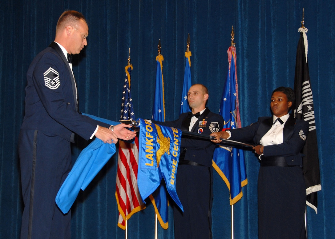 Air National Guard members Senior Master Sgt. Timothy J. Kumes, Master Sgt. Paul G. Rayman, and Tech. Sgt. Jeela S. Matthews perform a guidon exchange ceremony at The I. G. Brown Air National Guard Training and Education Center to signify the transition of the ANG EPME branch to its new name as the Paul H. Lankford Enlisted Professional Military Education Center December 16, 2008. (U.S. Air Force Photo by Master Sgt Kurt Skoglund)(Released)