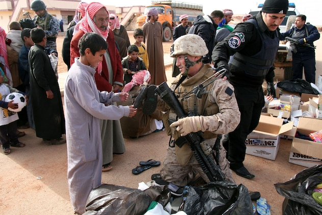Alongside Iraqi police, Sgt. Christopher Bambury, a vehicle commander with Mobile Assault Platoon 3, Weapons Company, 2nd Battalion, 25th Marine Regiment, Regimental Combat Team 5, gives a pair of shoes to an Iraqi boy during a distribution of clothing and other supplies to Bedouin families in Walej, Iraq on Dec. 26.  Bambury, a Reserve Marine on his second tour in Iraq, is also a New York City firefighter from Breezy Point, N.Y.::r::::n::