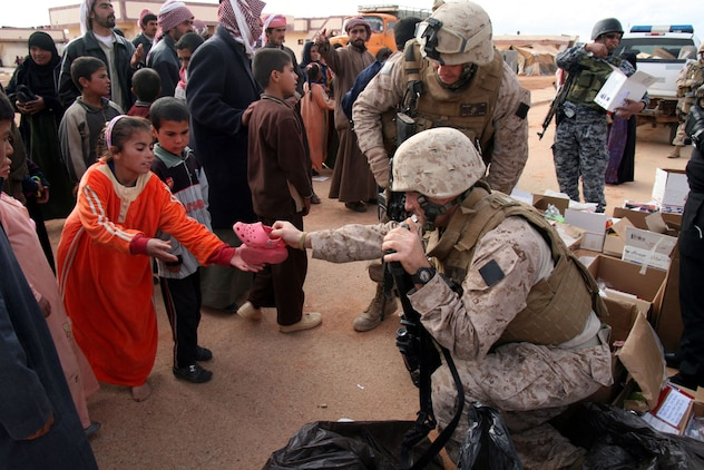 Sgt. Christopher Bambury, a vehicle commander with Weapons Company, 2nd Battalion, 25th Marine Regiment, Regimental Combat Team 5, gives a pair of shoes to an Iraqi girl during a distribution of clothing and other supplies to Bedouin families in Walej, Iraq on Dec. 26.  Bambury, a Reserve Marine on his second tour in Iraq, is also a New York City firefighter from Breezy Point, N.Y.  More than 60 pair of shoes were collected and mailed to Bamburyâ??s unit in Iraq by a teacher and students from a Long Island, N.Y. middle school.::r::::n::