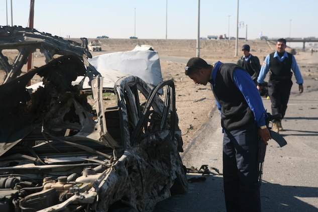 Iraqi police with the Karmah police station investigate a suicide attack and search for suspects on a local highway in Fallujah, Iraq, Dec. 28. Iraqi Security Forces were quick to respond to the situation and provided casualty assistance to injured personnel.